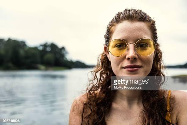 young woman wearing sunglasses at lake - カラーサングラス ストックフォトと画像