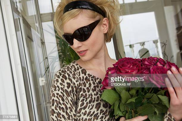 Young woman wearing sunglasses holding bunch of flowers