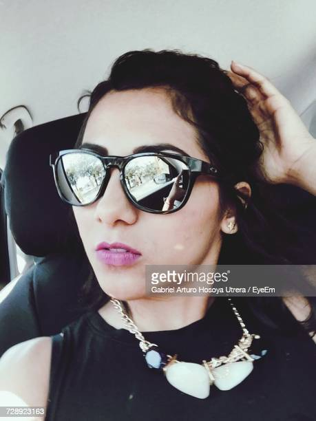 Young Woman Wearing Sunglasses In Car