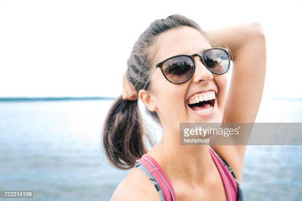 young woman wearing sunglasses laughing by sea, maine, usa - heshphoto stock pictures, royalty-free photos & images