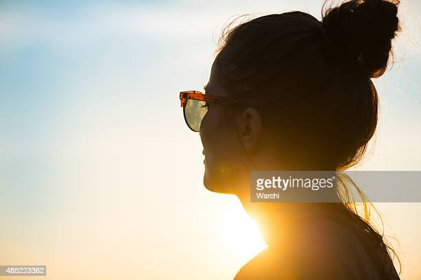 young woman  wearing sunglasses looking at sunset - solljus bildbanksfoton och bilder