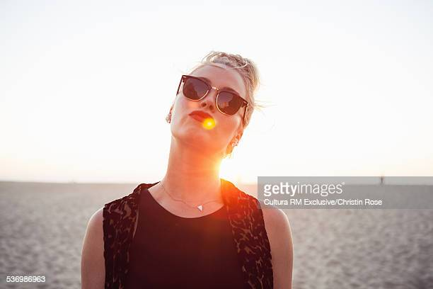 Young woman wearing sunglasses on beach, portrait