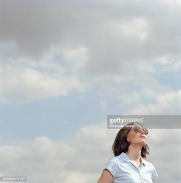 young woman wearing sunglasses outdoors, looking up - 半そで ストックフォトと画像