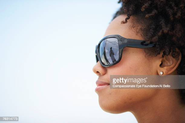 "young woman wearing sunglasses outdoors, profile, close-up - ""compassionate eye"" stock-fotos und bilder"