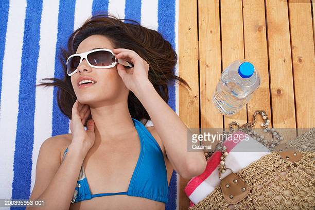 young woman wearing sunglasses, relaxing on beach deck - sdraiato foto e immagini stock