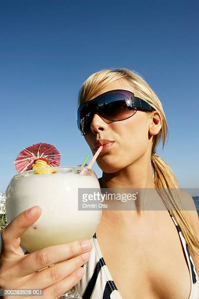 Young woman wearing sunglasses, sipping cocktail, close-up