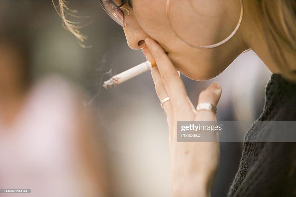 Young woman wearing sunglasses, smoking outdoors, close-up : Stock Photo