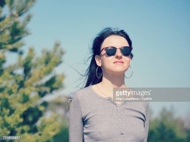 young woman wearing sunglasses standing against sky - {{relatedsearchurl('london eye')}} stock photos and pictures