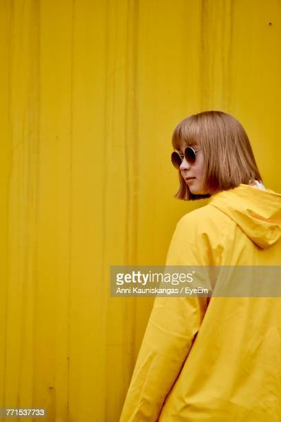 Young Woman Wearing Sunglasses Standing Against Yellow Corrugated Iron