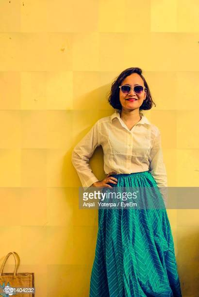 young woman wearing sunglasses standing against yellow wall in an indo western attire - etnia indo asiatica foto e immagini stock