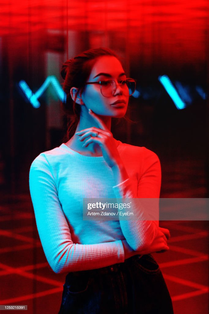 Young Woman Wearing Sunglasses Standing At Night : Stock Photo