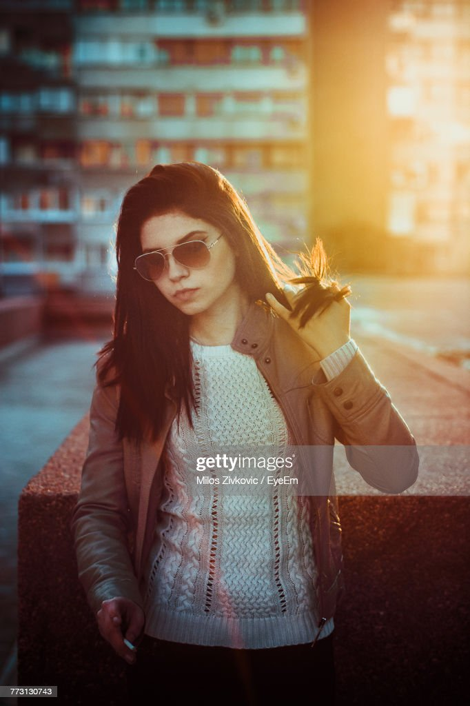 Young Woman Wearing Sunglasses Standing On Street In City : Photo