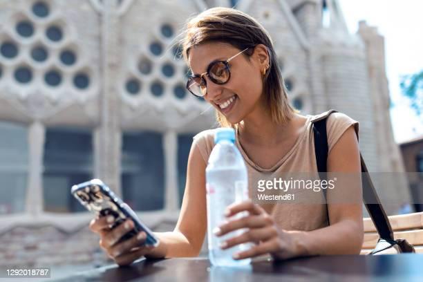 young woman wearing sunglasses using mobile phone while sitting against sagrada familia at barcelona, catalonia, spain - familia stock-fotos und bilder