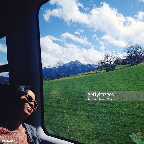 young woman wearing sunglasses watching grassy field through train window - saxony anhalt stock pictures, royalty-free photos & images