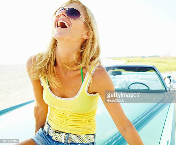 Young woman wearing sunglasses while sitting on car bonnet