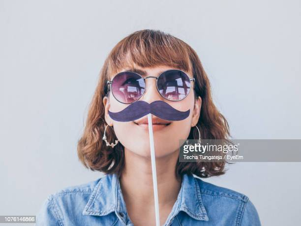 young woman wearing sunglasses with mustache prop against white background - 小道具 ストックフォトと画像