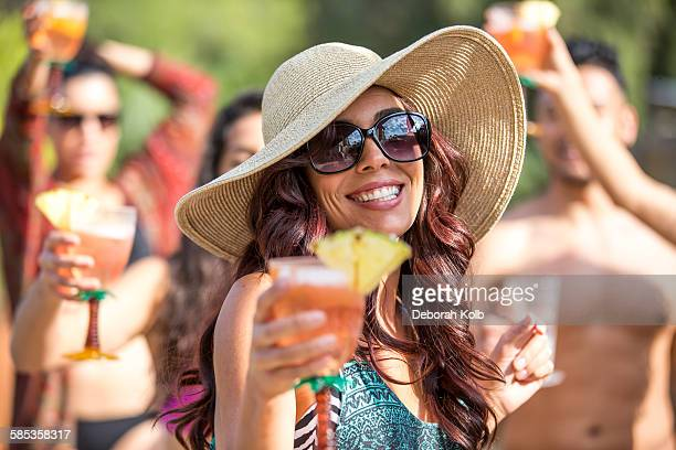 Young woman wearing sunhat drinking cocktail and dancing in garden