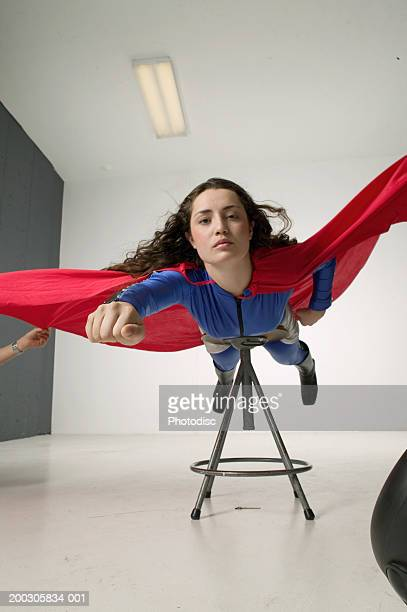 Young woman wearing superhero costume, posing in studio, portrait,, low angle view