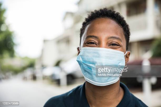 young woman wearing surgical mask in front of home - covid-19 ストックフォトと画像
