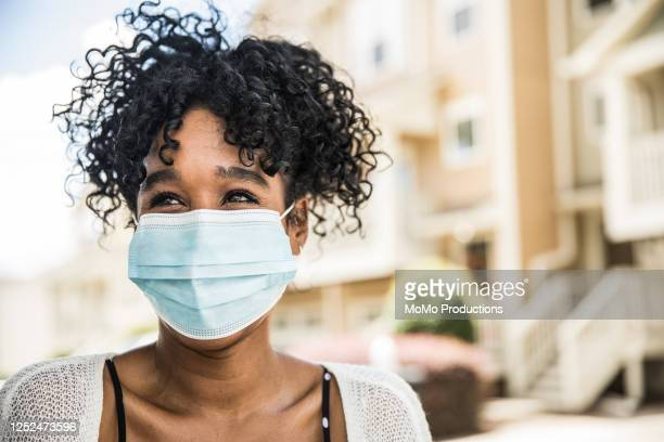 young woman wearing surgical mask in front of home - women stock pictures, royalty-free photos & images