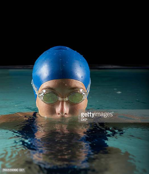 Young woman wearing swimming cap and goggles in pool, high section