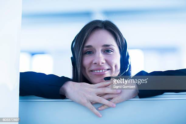young woman wearing telephone headset looking over partition screen at camera smiling - sigrid gombert stockfoto's en -beelden
