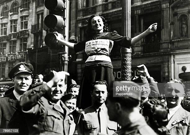 Young woman wearing the front cover of the Evening News is held aloft by Allied servicemen as the West End of London celebrates the end of conflict...