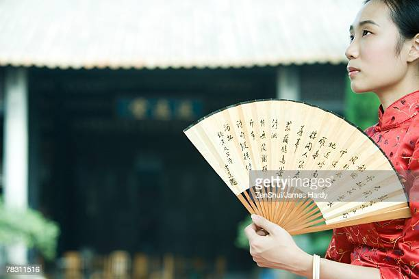young woman wearing traditional chinese clothing, holding fan, looking up - hand fan stock pictures, royalty-free photos & images