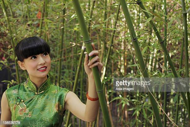 Young woman wearing traditional Chinese dress standing in bamboo forest