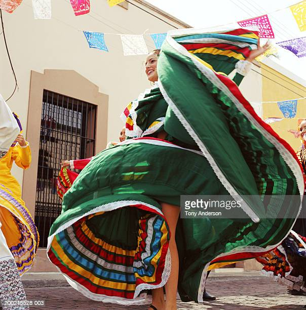 Young woman wearing traditional dress, dancing at fiesta