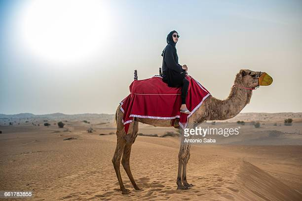 Young woman wearing traditional middle eastern clothes riding camel in desert, Dubai, United Arab Emirates