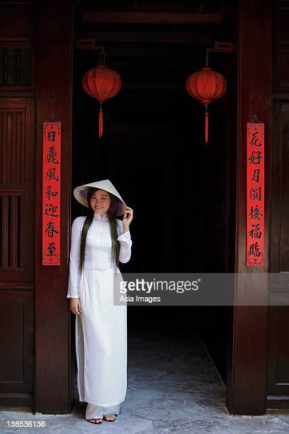Young woman wearing traditional Vietnamese outfit standing in front of a temple, Vietnam