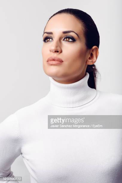 young woman wearing turtleneck against white background - turtleneck stock pictures, royalty-free photos & images