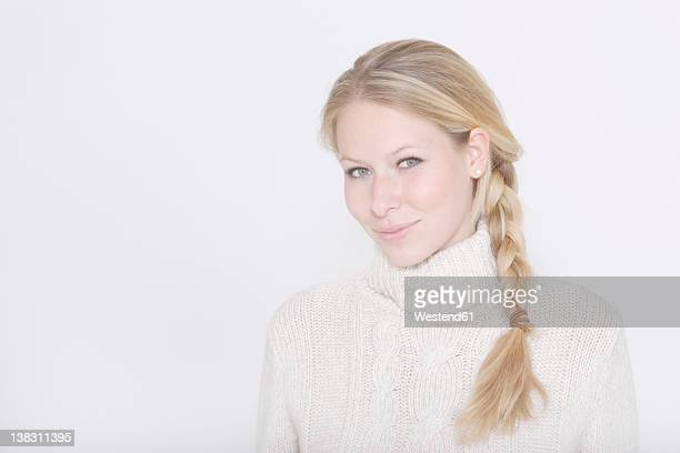 Young woman wearing turtleneck jumper and braided hairstyle against white background, portrait, smiling
