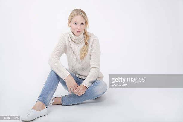 Young woman wearing tutleneck jumper sitting on white background, smiling, portrait