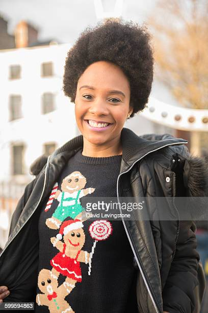 young woman wearing ugly christmas jumper - ugly black women stock photos and pictures