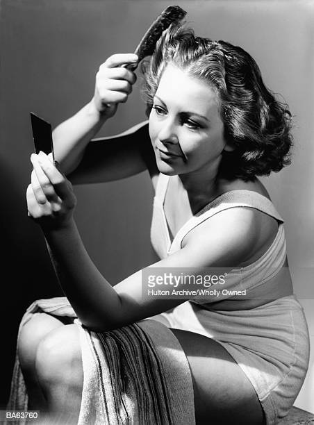 Young woman wearing underwear, brushing hair (B&W)