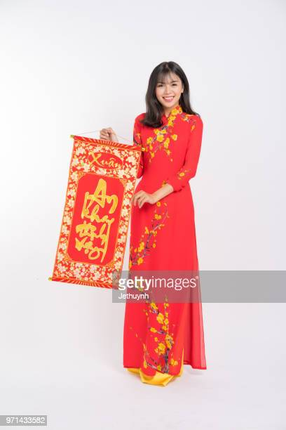 Young woman wearing Vietnamese Red color Ao Dai, smiling, holding a lucky scroll for new year