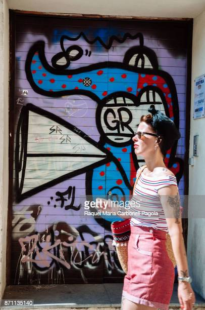 Young woman wearing vintage hipster look walking by urban graffiti