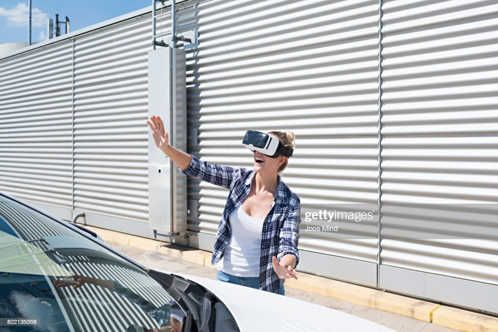 young woman wearing VR Glasses at car park : Stock Photo