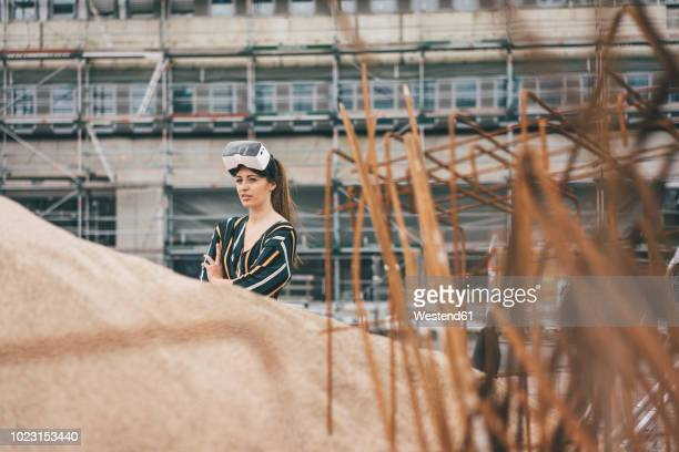 Young woman wearing VR glasses at construction site