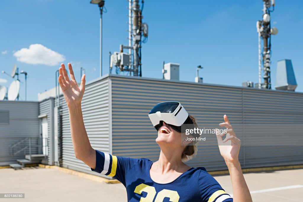 young woman wearing VR Glasses at rooftop : Stock Photo