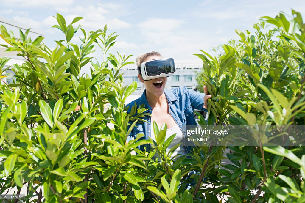 young woman wearing VR Glasses exploring plants : Stock Photo