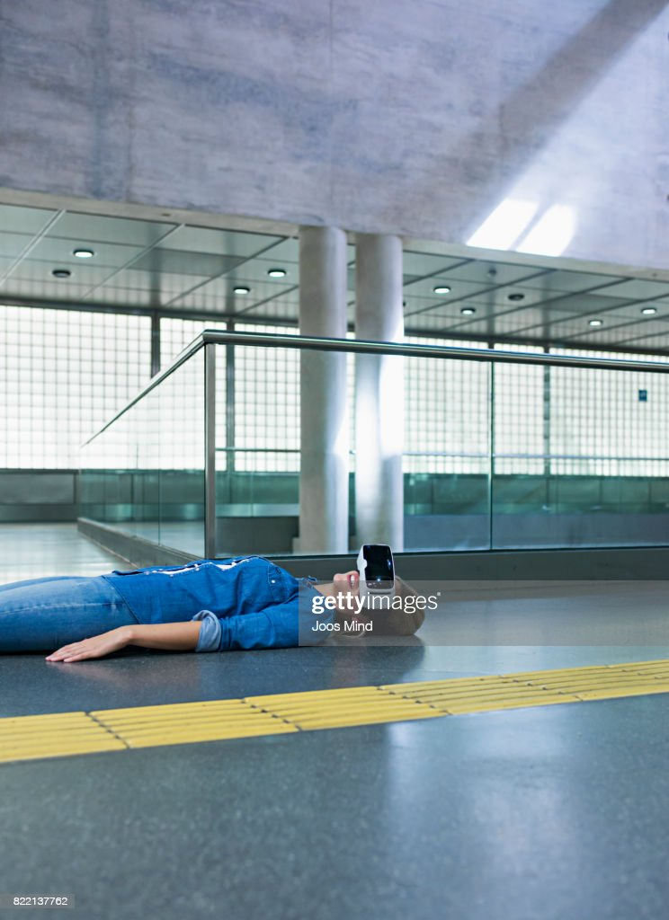 young woman wearing VR Glasses lying on floor : Stock Photo