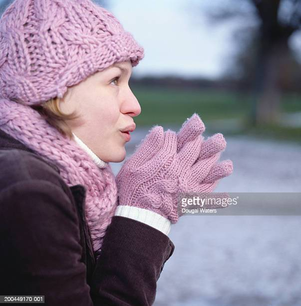 Young woman wearing warm clothing, rubbing hands, outdoors, side view