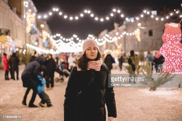 young woman wearing warm clothing standing in brightly lit street - good; times bad times stock pictures, royalty-free photos & images