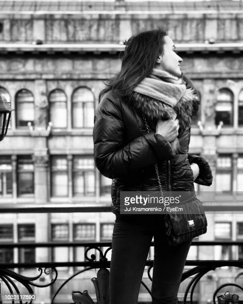 Young Woman Wearing Warm Clothing While Standing Against Building In City