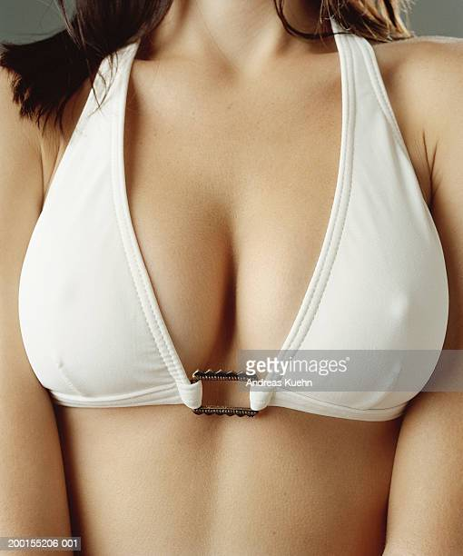 young woman wearing white bikini top, mid section, close-up - busen nahaufnahme stock-fotos und bilder