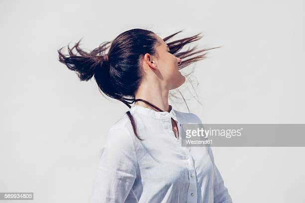 Young woman wearing white blouse tossing her ponytail in front of white background