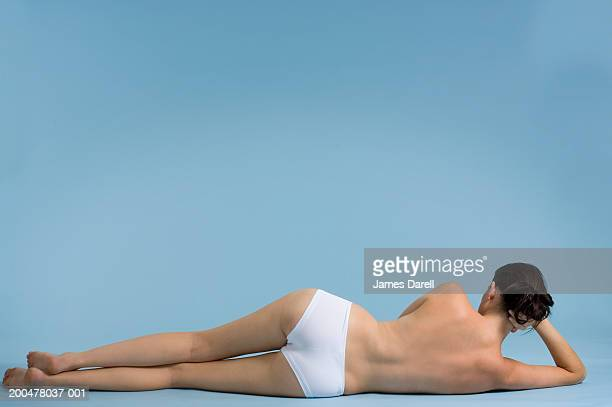 Young woman wearing white briefs lying on floor, rear view